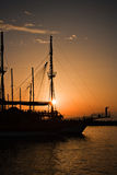 Sailing ship silhouetted against amber sky Royalty Free Stock Photo