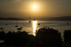 SAILING SHIP ON THE SUNSET. A Sailing boat passes through the sun path on a summer sunset in Ouranoupoli Halkidiki - Greece Stock Photos
