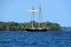 Sailing ship with tropical island in background Royalty Free Stock Photos