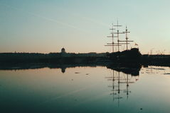 Sailing-ship and twilights. Sailing-ship reflecting in water in evening light Stock Image
