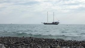 Sailing ship with two masts moving in the water from right to left. Sea coast with stones and pebbles at the front. Cloudy summer day somewhere near Sochi stock video footage