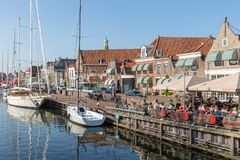 Sailing ships in harbor Enkhuizen with people relaxing at terrace Royalty Free Stock Photos
