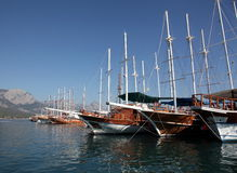 Sailing ships in harbour. A line of sailing ships in Mediterranian harbour in Kemer against the backdrop of mountains Stock Image