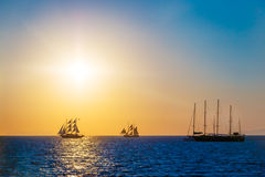 Sailing ships on the sea in sunset. Sailing ships on the sea in colorful sunset royalty free stock photography
