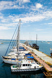 Sailing ships and yachts stand moored in marina port Stock Photos