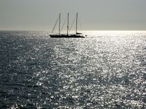 Sailing in silver sea. A sailing boat in silver sea Royalty Free Stock Image