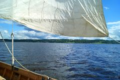 Sailing on skiff. View from the board of skiff during sailing. Between the sail and the ship`s side are visible waves and a far shore Stock Photography
