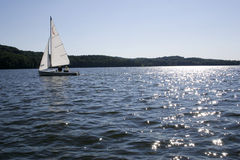 Sailing on sparkling lake. Sailboat on lake with sun spakling onto water in Pennsylvania Royalty Free Stock Photos