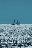 Sailing on Sparkling Seas. Two sailboats passing on the Pacific Ocean at the end of the day royalty free stock photo