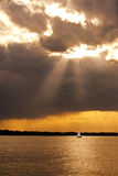 Sailing a Stormy Chesapeake. A sailboat on the Chesapeake Bay at sunset with a stormy sky royalty free stock images