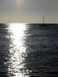 Sailing in the Sun. Lone sailboat off the coast of Waikiki Stock Photo