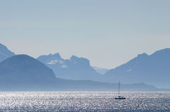 Sailing during sunrise, Norway. Sail boat in the Vestfjords. At the background the island Hamarøy, one of the islands in the sest  of Nordland in Norway, seen Stock Image