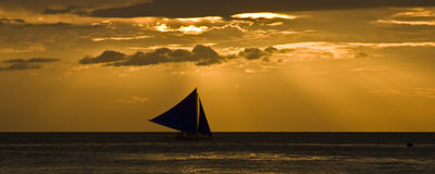 Sailing at Sunset. Sun rays shine down on a banca boat sailing at sunset in tropical paradise Stock Photo