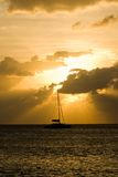 Sailing into the Sunset. Sunset with a Silhouette of a Sailboat in Grand Cayman Royalty Free Stock Image