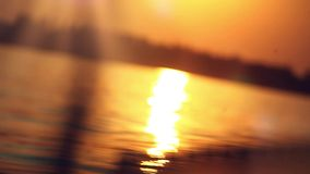 Sailing into the sunset on blurred reflected water stock footage