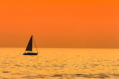 Sailing at Sunset. This image of a Sailboat sailing at sunset was captured from the beach in Oceanside, California.  The boat was headed towards the Oceanside Royalty Free Stock Images