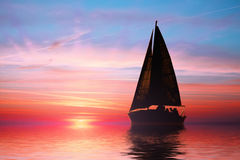 Sailing at sunset on the ocean royalty free stock photography