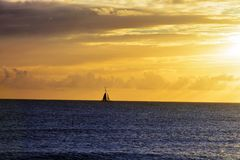 Sailing at sunsetin the ocean stock image