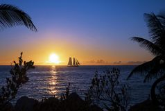 Sailing At Sunset. Seascape of a silhouetted sailboat sailing at sunset with palm tree silhouettes in the foreground Royalty Free Stock Image