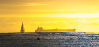 Sailing sunsets. Sailboats, surfers, and freight ships Stock Images