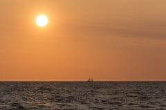 Sailing tallship on horizon and large sun. Sailing tallship on the horizon under a large sun. A three masted barque far away on the Baltic sea. The Tall Ships' Stock Image