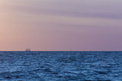 Sailing tallship on the horizon. A three masted barque far away in summernight light. The Tall Ships' Races 2013 Stock Photography