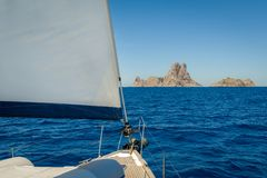 Sailing to freedom. Sailing boat bow with hoisted sails which is going to rocky islands. Spain Royalty Free Stock Images