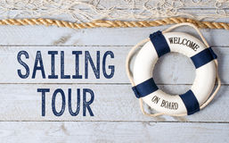 Sailing tour. Text 'sailing tour' on white painted wooden boards and 'welcome on board' on white lifebuoy with rough ship's rope placed above it Royalty Free Stock Image