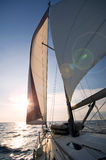 Sailing towards sunset. Yacht on the see heading toward sunset Stock Photos