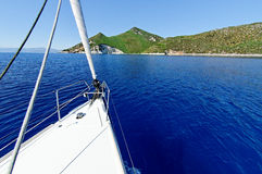 Sailing trip. Sailing on a yacht across a calm blue sea towards the One House Bay, Atokos island Royalty Free Stock Photos