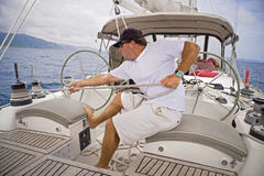 Sailing in the tropics. Man sailing a sailboat pulling the ropes tight Royalty Free Stock Photography