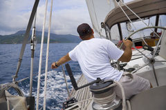 Sailing in the tropics. Man sailing a sailboat in the tropics with tropical mountain in background Stock Photo