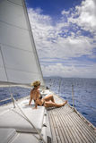 Sailing in the tropics. Attractive woman sitting on the front of large and luxurious sailboat sailing through the tropics Stock Images