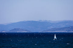 Sailing on the turkish aegean sea. A little sail boat is sailing on the blue aegean sea of Cesme Izmir - Turkey Royalty Free Stock Images
