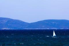 Sailing on the turkish aegean sea. A little sail boat is sailing on the blue aegean sea of Cesme Izmir - Turkey Stock Images