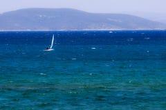 Sailing on the turkish aegean sea. A little sail boat is sailing on the blue aegean sea of Cesme Izmir - Turkey Royalty Free Stock Image
