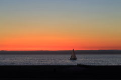 Sailing at twilight. Yacht sailing by the beach after the sunset Royalty Free Stock Photo