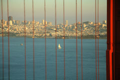 Golden Gate Bridge. Scenic view of San Francisco skyline and Bay viewed through cables of Golden Gate Bridge, California, U.S.A Royalty Free Stock Images