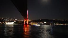 Sailing under Istanbul`s bridge at night stock video footage