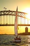 Sailing under Sydney Harbour Bridge at sunset Royalty Free Stock Photo