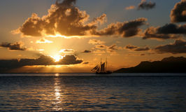 Sailing vacation in sunset rays. This is the picture of beautiful sunset over sea and island.  The golden sun rays are coming through clouds .The sea surface is Stock Photos