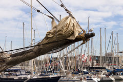 Sailing vessel bowsprit. Bowsprit of a sailing ship with furled jibs and seagull  in the harbor with  moored yachts in background Royalty Free Stock Photos