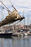 Sailing vessel bowsprit. Bowsprit of a sailing ship with furled jibs and seagull  in the harbor with  moored yachts in background Stock Photography