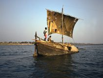 A Sailing vessel on the Ganges. Transporting goods with a rugged sailing boat at the Ganges near Banaras Varanasi in India. You may wonder it sails at all, heavy royalty free stock photography