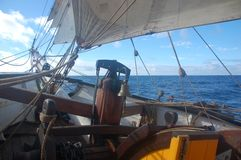 Sailing vintage wooden sailboat on the ocean with blue sky and clouds stock image
