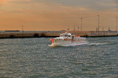Sailing white motorboat in port of Venice at sunrise. Venice, Italy - August 21, 2015: Sailing white passenger motorboat in port of Venice at sunrise royalty free stock photos