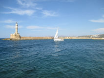 Sailing White Yacht near the Lighthouse at the Old Venetian Harbour of Chania, Crete Island, Greece Stock Image