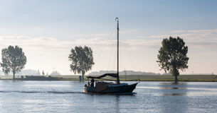 Sailing on a windless morning. It is an early autumn morning and there is still some morning mist above the river Stock Images