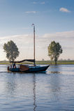 Sailing on a windless morning. It is an early autumn morning and there is still some morning mist above the river Stock Photography