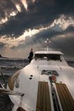 Sailing on Yacht. A man sailing on his yacht, under a cloudy sky Royalty Free Stock Images